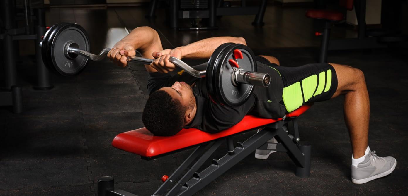 Mann im Fitnessstudio führt Übung im liegen aus und hält Hantel in beiden Händen.